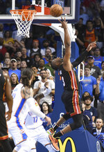 Miami Heat guard Dwyane Wade (3) shoots over Oklahoma City Thunder center Steven Adams in the second half of an NBA basketball game Monday, March 18, 2019, in Oklahoma City. (AP Photo/Kyle Phillips)