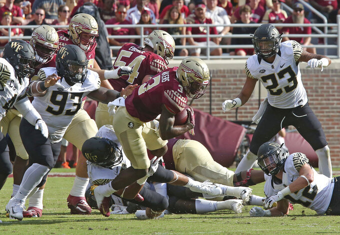 Florida State's Cam Akers, center, struggles to pick up yardage in the second quarter of an NCAA college football game with Wake Forest, Saturday, Oct. 20, 2018 in Tallahassee, Fla. Florida State won 38-17. (AP Photo/Steve Cannon)