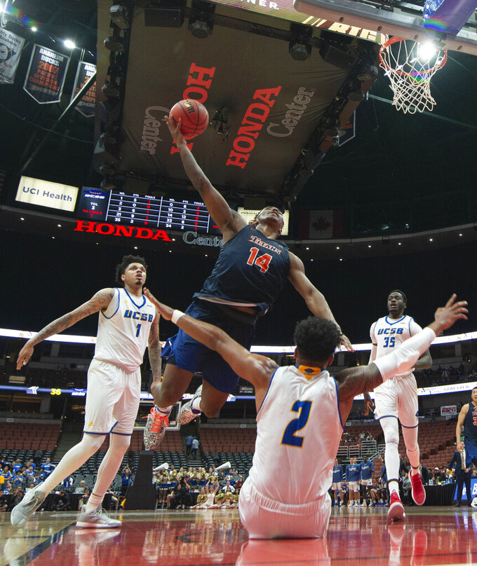 Cal State Fullerton guard Khalil Ahmad, top, shoots over UC Santa Barbara forward Jarriesse Blackmon during the second half of an NCAA college basketball game at the Big West men's tournament in Anaheim, Calif., Friday, March 15, 2019. (AP Photo/Kyusung Gong)