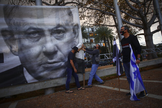 FILE - In this April 25, 2020 file photo, demonstrators wearing protective face masks amid concerns over the country's coronavirus outbreak, hang a banner showing Israeli Prime Minister Benjamin Netanyahu during