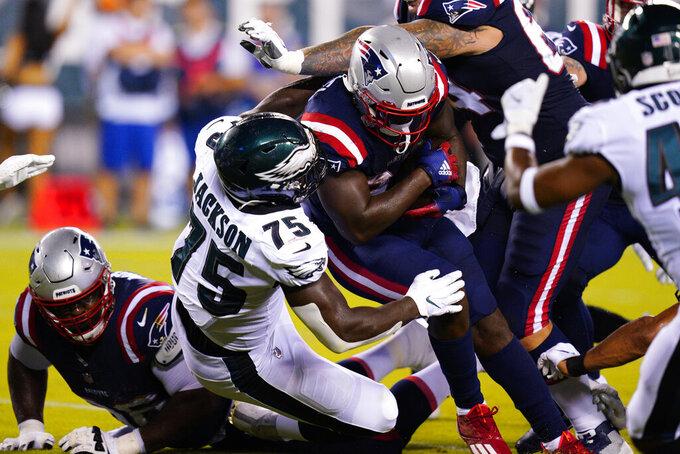 New England Patriots' Sony Michel, center, gets stopped by Philadelphia Eagles' Tarron Jackson during the first half of a preseason NFL football game Thursday, Aug. 19, 2021, in Philadelphia. (AP Photo/Chris Szagola)