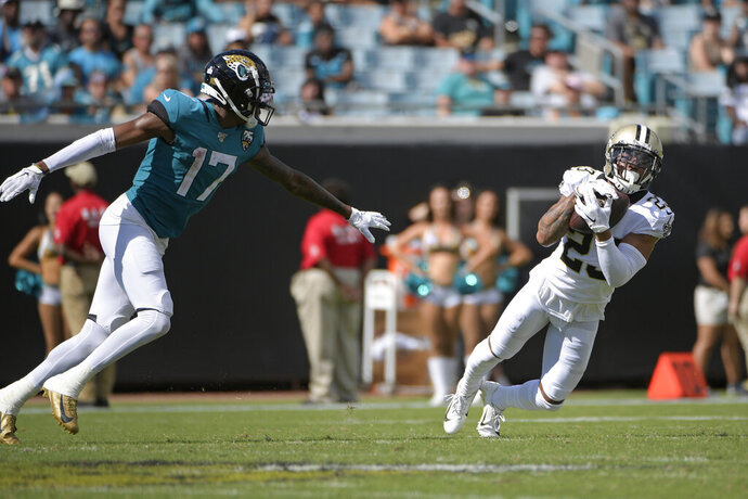 FILE - In this Oct. 13, 2019, file photo, New Orleans Saints cornerback Marshon Lattimore, right, intercepts a pass in front of Jacksonville Jaguars wide receiver D.J. Chark (17) during the second half of an NFL football game in Jacksonville, Fla. Lately, Lattimore hasn't had to discuss many failures in pass coverage, even though he spends significant portions of every game covering opponents' top receivers. His next challenge comes Sunday in Chicago, whose receiver corps is led by Allen Robinson. The last three receivers Lattimore covered--Jacksonville's Chark, Tampa Bay's Mike Evans and Dallas' Amari Cooper--did little to help their teams in those games. (AP Photo/Phelan M. Ebenhack, File)