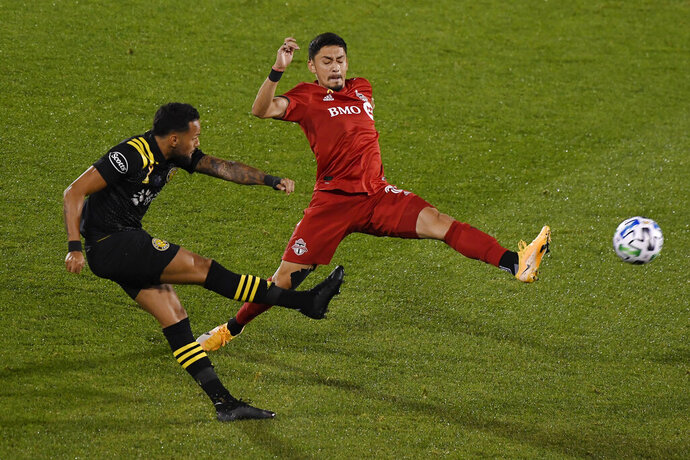 Toronto FC's Mark Delgado, right, challenges Columbus Crew's Artur during the first half of an MLS soccer match, Sunday, Sept. 27, 2020, in East Hartford, Conn. (AP Photo/Jessica Hill)