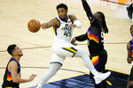 Utah Jazz guard Donovan Mitchell (45) dishes off as Phoenix Suns forward Jae Crowder defends during the second half of an NBA basketball game, Wednesday, April 7, 2021, in Phoenix. (AP Photo/Matt York)