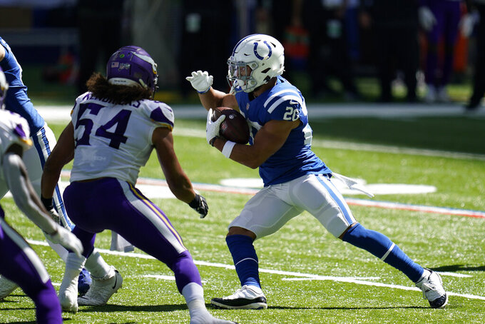 Indianapolis Colts' Jonathan Taylor (28) runs against Minnesota Vikings' Eric Kendricks (54) during the first half of an NFL football game, Sunday, Sept. 20, 2020, in Indianapolis. (AP Photo/Michael Conroy)