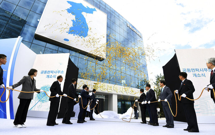 FILE - In this Sept. 14, 2018, file photo, South Korea's Unification Minister Cho Myoung-gyon, center left, and Ri Son Gwon, chairman of the North's Committee for the Peaceful Reunification, center right, attend at an opening ceremony for two Koreas' first liaison office in Kaesong, North Korea. North Korea abruptly withdrew its staff from an inter-Korean liaison office in the North on Friday, Seoul officials said on Friday, March 22, 2019. (Korea Pool/Yonhap via AP, File)