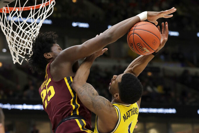 Minnesota's Daniel Oturu (25) blocks a shot by Michigan's Charles Matthews (1) during the second half of an NCAA college basketball game in the semifinals of the Big Ten Conference tournament, Saturday, March 16, 2019, in Chicago. (AP Photo/Nam Y. Huh)
