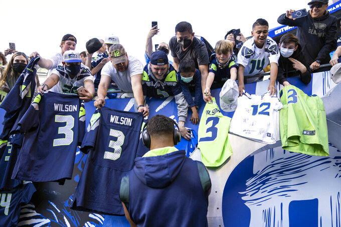 FILE - In this Aug. 28, 2021, file photo, Seattle Seahawks quarterback Russell Wilson signs autographs for fans before an NFL football game against the Los Angeles Chargers in Seattle. Fans attending most pro sporting events in Seattle will soon be required to show proof they've been vaccinated against COVID-19 or that they've tested negative for the virus. The NFL's Seahawks, MLS's Sounders, NHL's Kraken and the University of Washington all announced updated policies Tuesday, Sept. 7, 2021, for fans attending games this season.  (AP Photo/Stephen Brashear, File)