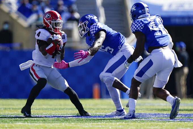 Georgia running back James Cook (4) is tackled by Kentucky linebacker DeAndre Square (5) during the second half of an NCAA college football game, Saturday, Oct. 31, 2020, in Lexington, Ky. (AP Photo/Bryan Woolston)
