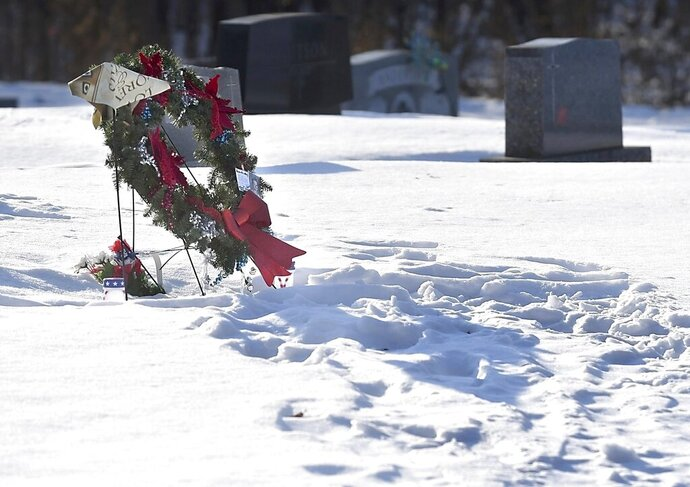 Family and friends mark Landon Gran's gravestone with a wreath and a flag at a cemetery east of Norseland, Minn. Landon's mother, Michele, said his friends continue to visit after he died inside a grain bin Aug. 14. (Pat Christman)/The Free Press via AP)