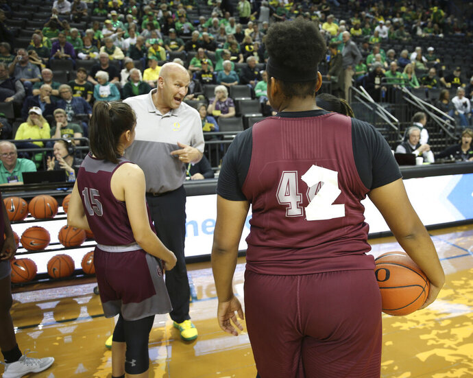 Oregon head coach Kelly Graves talks to Texas Southern players before an NCAA college basketball game in Eugene, Ore., Saturday, Nov. 16, 2019. Texas Southern's uniforms went missing, forcing them to improvise with practice jerseys and athletic tape. (AP Photo/Chris Pietsch)