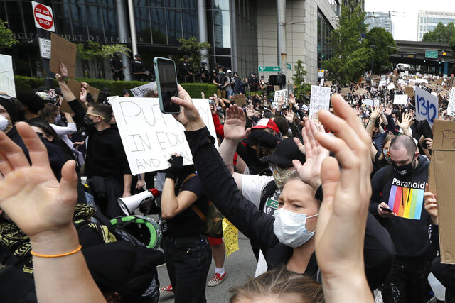 Demonstrators march toward Seattle City Hall Wednesday, June 3, 2020, in Seattle, following protests over the death of George Floyd, a black man who died in police custody in Minneapolis. (AP Photo/Elaine Thompson)