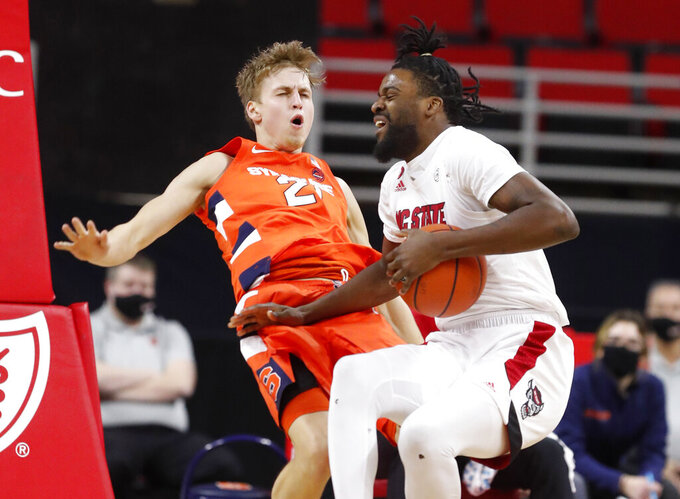 North Carolina State's D.J. Funderburk (0) is called for the foul after running into Syracuse's Marek Dolezaj (21) during the first half of an NCAA college basketball game, Tuesday, Feb. 9, 2021 in Raleigh, N.C. (Ethan Hyman/The News & Observer via AP, Pool)