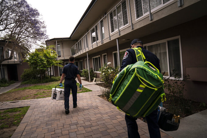Torrance firefighters Trevor Borello, left, and Alessandro Demuro carry a cooler containing the Pfizer COVID-19 vaccine and medical equipment as they walk to an apartment to inoculate two sisters who have  muscular dystrophy, Wednesday, May 12, 2021, in Torrance, Calif. Teamed up with the Torrance Fire Department, Torrance Memorial Medical Center started inoculating people at home in March, identifying people through a city hotline, county health department, senior centers and doctor's offices, said Mei Tsai, the pharmacist who coordinates the program. (AP Photo/Jae C. Hong)