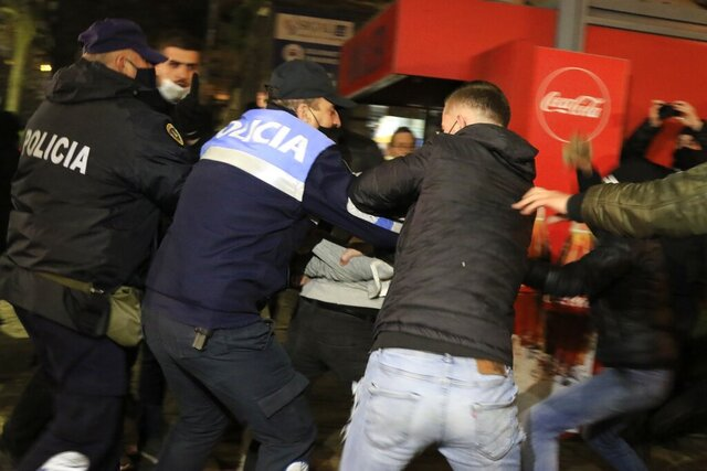 Albanian police detain a protester as others try to release him during clashes in Tirana, Friday, Dec. 11, 2020. Albanian demonstrators clashed in the third day on Friday protesting for the death of a 25-year-old man shot dead by a police officer. (AP Photo/Hektor Pustina)