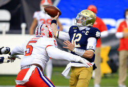 Notre Dame quarterback Ian Book (12) is pressured by Clemson defensive end K.J. Henry (5) during the first half of the Atlantic Coast Conference championship NCAA college football game, Saturday, Dec. 19, 2020, in Charlotte, N.C. (AP Photo/Brian Blanco)