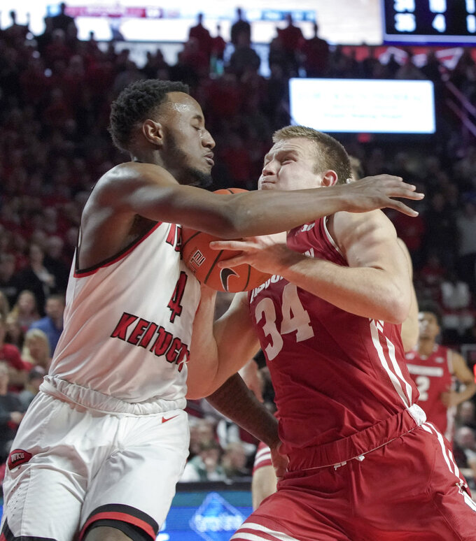 Western Kentucky guard Josh Anderson (4) defends against Wisconsin guard Brad Davison (34) during the second half of an NCAA college basketball game Saturday, Dec. 29, 2018, in Bowling Green, Ky. (AP Photo/Tim Broekema)