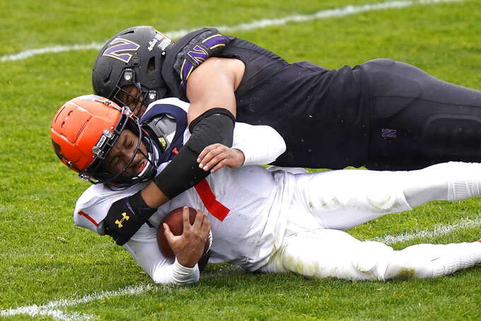 Illinois quarterback Isaiah Williams, left, is tackled by Northwestern defensive end Earnest Brown IV during the first half of an NCAA college basketball game in Evanston, Ill., Saturday, Dec. 12, 2020. (AP Photo/Nam Y. Huh)