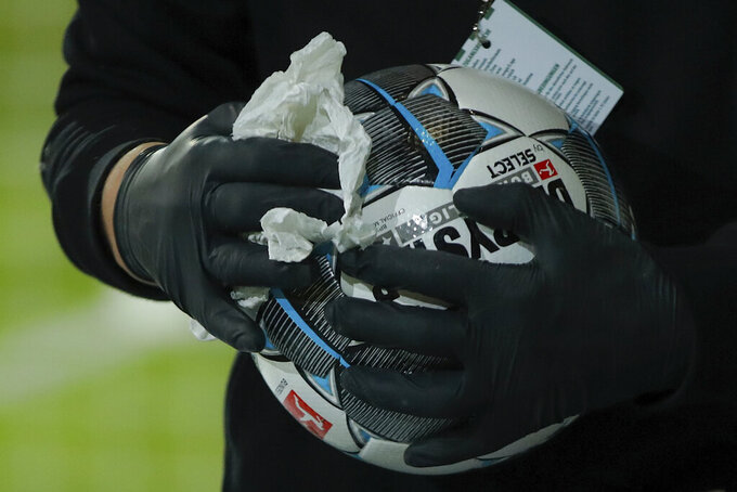 Staff members clean and disinfect the match balls after the the German first division Bundesliga soccer match, with Union Berlin facing FSV Mainz 05, being played without spectators because of the coronavirus, in Berlin, Germany, Wednesday May 27, 2020. (Odd Andersen / Pool via AP)
