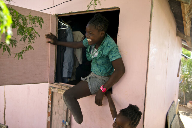 In this Jan. 3, 2020 photo, Rose-Berline Thomas sits in a window to speak with her mother outside at their home in Canaan, a district in Croix des Bouquets, Haiti, created for people who lost their homes in the earthquake 10 years ago. Rose-Berline Thomas was 2-years-old when the earthquake collapsed her family's home on top of her, crushing her foot. (AP Photo/Dieu Nalio Chery)