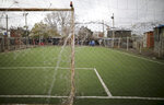 """A soccer field is closed as health officials walk along its perimeter in the Villa Azul neighborhood, where officials isolated residents for strick quarantine after many residents tested positive for COVID-19 on the outskirts of Buenos Aires, Argentina, Monday, May 25, 2020. An informal """"lightning"""