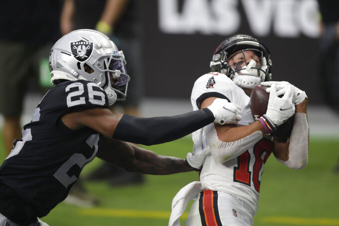 Tampa Bay Buccaneers wide receiver Scott Miller (10) catches a pass for a touchdown over Las Vegas Raiders cornerback Nevin Lawson (26) during the first half of an NFL football game, Sunday, Oct. 25, 2020, in Las Vegas. (AP Photo/Isaac Brekken)