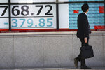 A man looks at an electronic stock board of a securities firm in Tokyo, Thursday, Nov. 21, 2019. Shares skidded Thursday in Asia after moderate declines on Wall Street as anxious mounted over the possibility the U.S. and China may not reach a trade deal before next year. (AP Photo/Koji Sasahara)