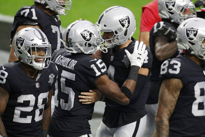 Las Vegas Raiders quarterback Derek Carr, center right, embraces wide receiver Nelson Agholor (15) after Agholor made a touchdown catch against the Indianapolis Colts during the first half of an NFL football game, Sunday, Dec. 13, 2020, in Las Vegas. (AP Photo/Isaac Brekken)