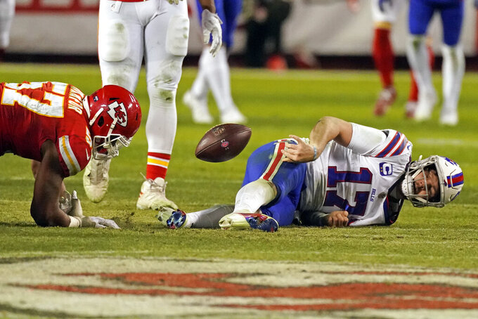 Buffalo Bills quarterback Josh Allen (17) tosses the ball towards Kansas City Chiefs defensive end Alex Okafor (57) after being sacked during the second half of the AFC championship NFL football game Sunday, Jan. 24, 2021, in Kansas City, Mo. (AP Photo/Charlie Riedel)
