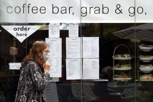 A patron adjusts her mask after ordering food from a walk-up window at Plant City restaurant, in Providence, R.I., Monday, May 18, 2020. Rhode Island allowed restaurants to provide service with outdoor seated dinning Monday for the first time since the beginning of the government imposed lockdown due to the coronavirus pandemic. (AP Photo/Steven Senne)
