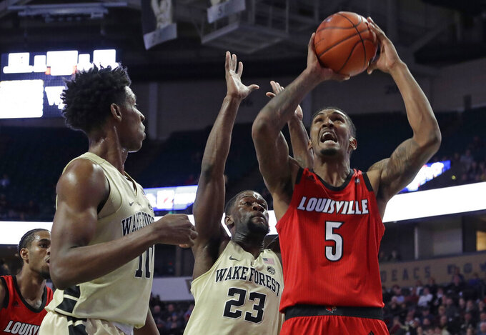 Louisville's Malik Williams (5) drives to the basket against Wake Forest's Chaundee Brown (23) and Jaylen Hoard (10) during the first half of an NCAA college basketball game in Winston-Salem, N.C., Wednesday, Jan. 30, 2019. (AP Photo/Chuck Burton)