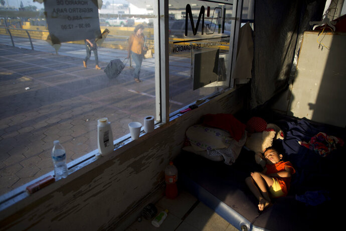 Hassan Bustio Paz, 5, from Honduras, rests inside the room he is sharing with his mother and other pregnant migrants, at the entrance to the Puerta Mexico international bridge, in Matamoros, Tamaulipas state, Mexico, Thursday, June 27, 2019. Hassan's mother said she is one of at least four migrants who were told they could not put their names on the months-long list to request asylum at this border post, since they did not obtain Mexican papers after crossing the southern border.(AP Photo/Rebecca Blackwell)