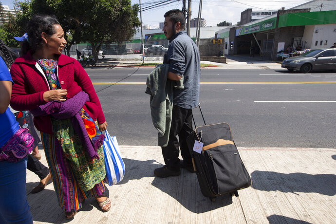 A woman looks over at a Guatemalan man who was deported from the United States, as he waits for a taxi after arriving in Guatemala City, Thursday, Nov. 21, 2019.  Guatemala's Foreign Ministry said a Honduran asylum seeker has also been returned by the United States to pursue asylum in Guatemala for the first time under an agreement signed in July. The Honduran man, who was not identified, had reached the U.S. border but was sent to Guatemala Thursday. (AP Photo/Moises Castillo)