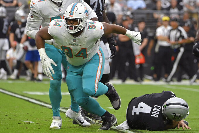 Miami Dolphins defensive end Christian Wilkins (94) celebrates after sacking Las Vegas Raiders quarterback Derek Carr (4) during the first half of an NFL football game, Sunday, Sept. 26, 2021, in Las Vegas. (AP Photo/David Becker)