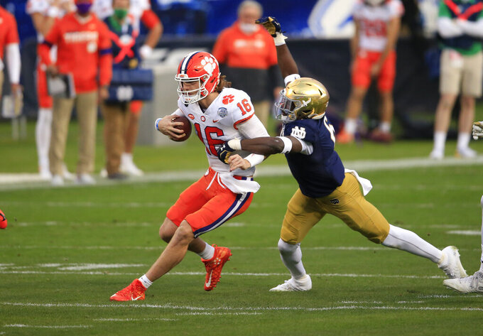 Clemson quarterback Trevor Lawrence (16) is stopped on a carry by Notre Dame linebacker Jeremiah Owusu-Koramoah (6) during the first half of the Atlantic Coast Conference championship NCAA college football game, Saturday, Dec. 19, 2020, in Charlotte, N.C. (AP Photo/Brian Blanco)