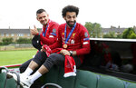 Liverpool's Dejan Lovren, left, and Mohamed Salah ride an open top bus during the Champions League Cup Winners Parade in Liverpool, England, Sunday June 2, 2019.  Liverpool is champion of Europe for a sixth time after beating Tottenham 2-0 in the Champions League final played in Madrid Saturday. (Barrington Coombs/PA via AP)