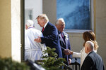 From left, Reverend Bruce McPherson and President Donald Trump walk together as head usher James Czerwonky greets first lady Melania Trump at they arrive to attend service at Saint John's Church in Washington, Sunday, March 17, 2019. (AP Photo/Carolyn Kaster)