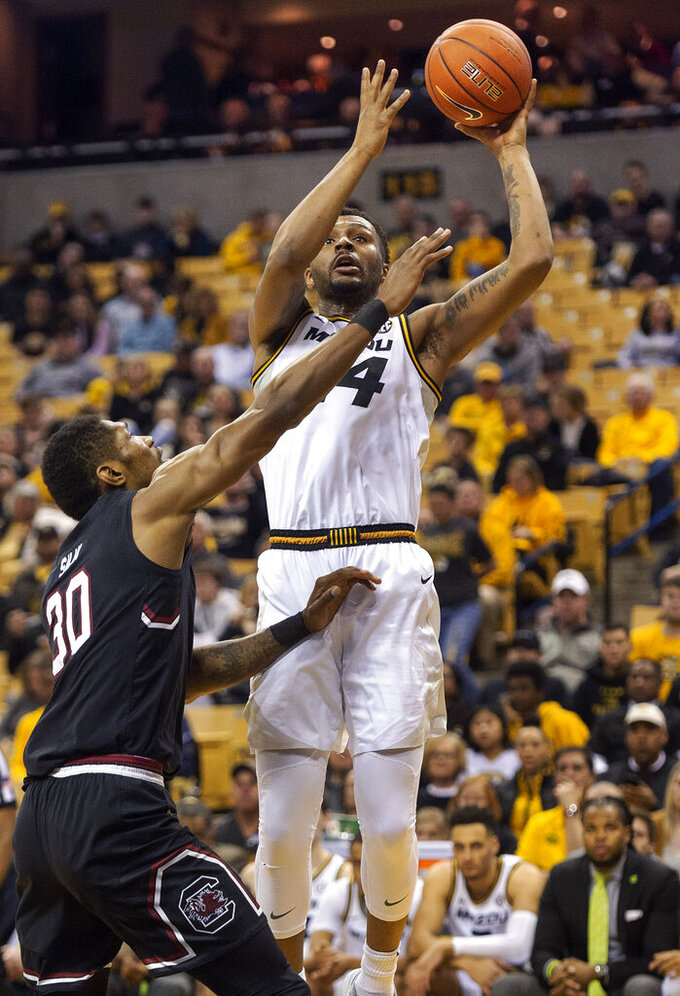 Missouri's Kevin Puryear, right, shoots over South Carolina's Chris Silva, left, during the second half of an NCAA college basketball game Saturday, March 2, 2019, in Columbia, Mo. Missouri won the game 78-63. (AP Photo/L.G. Patterson)