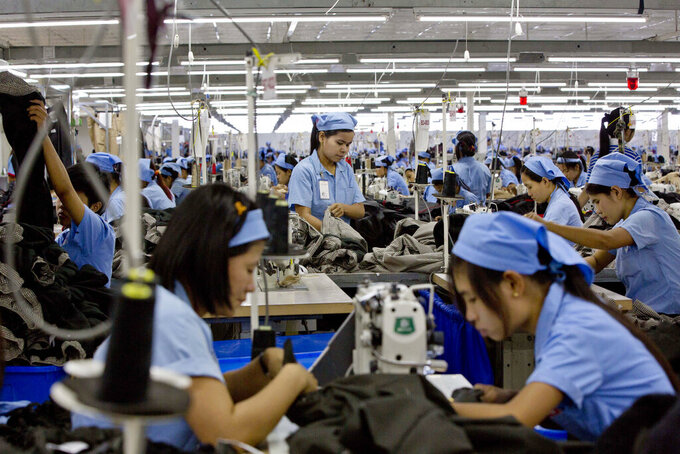 FILE  - In this Sept. 29, 2015, file photo, workers in the Great Forever factory stitch clothes in the Hlaing Tharyar industrial zone outside Yangon, Myanmar. Garment workers in Myanmar are urging major international brands to denounce the recent military coup there and put more pressure on factories to protect workers from being fired or harassed - or worse arrested and killed for participating in protests. (AP Photo,File)