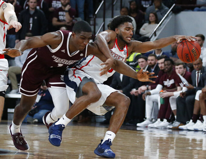 Mississippi guard Blake Hinson, right, recovers a loose ball as Mississippi State forward Reggie Perry, left, falls in the first half of an NCAA college basketball game, Saturday, Jan. 12, 2019 in Starkville, Miss. (AP Photo/Rogelio V. Solis)