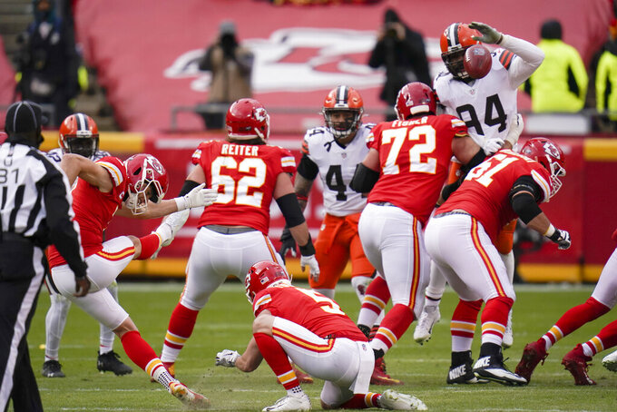 Kansas City Chiefs place kicker Harrison Butker, left, kicks a 50-yard field goal during the first half of an NFL divisional round football game against the Cleveland Browns, Sunday, Jan. 17, 2021, in Kansas City. (AP Photo/Jeff Roberson)