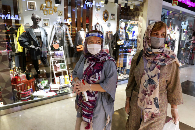 Women wearing protective face masks and gloves to help prevent the spread of the coronavirus shop at the Kourosh Shopping Center in Tehran, Iran, Monday, April 20, 2020. Iran on Monday began opening intercity highways and major shopping centers to stimulate its sanctions-choked economy, gambling that it has brought under control its coronavirus outbreak — one of the worst in the world — even as some fear it could lead to a second wave of infections. (AP Photo/Vahid Salemi)