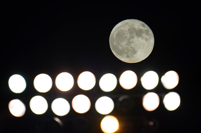 A rare Halloween blue moon moon rises over a bank of lights at Falcon Stadium in the second half of an NCAA college football game between Air Force and Boise State, Saturday, Oct. 31, 2020, at Air Force Academy, Colo. (AP Photo/David Zalubowski)