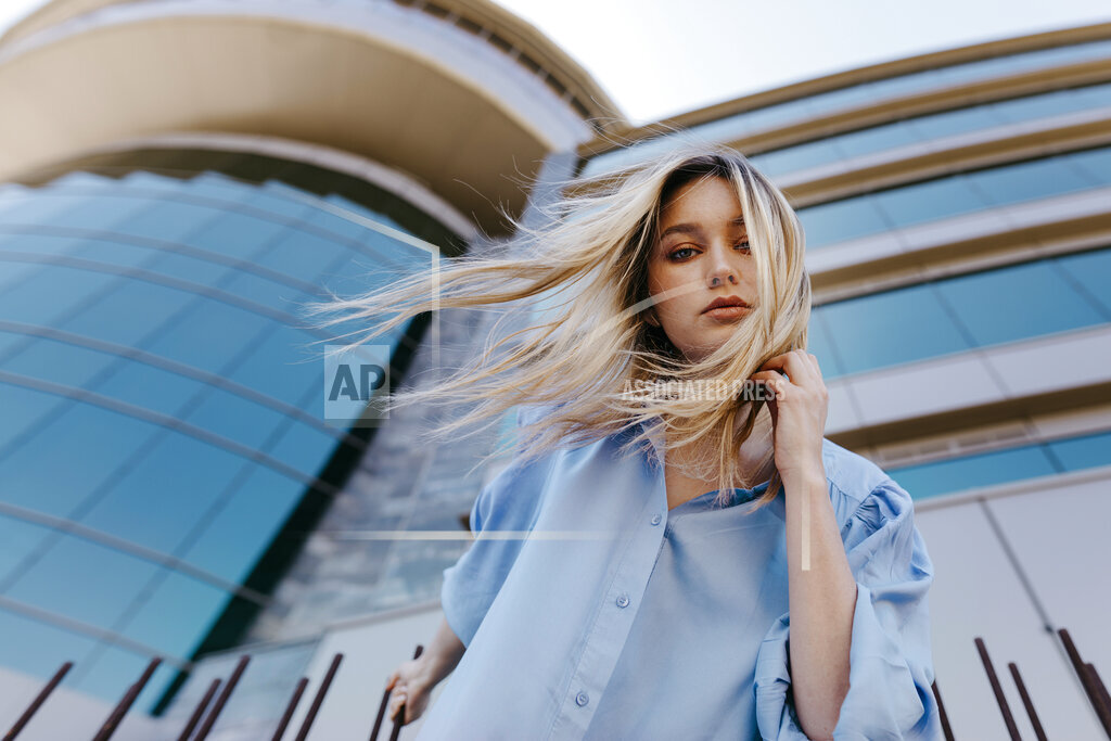 Beautiful young woman with tousled hair standing in front of modern building