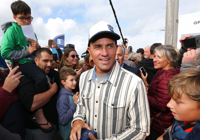 FILE - In this Oct. 9, 2019, file photo, surfer Kelly Slater is surrounded by fans after he leaves his footprint cement slab at Anglet Surf Avenue, in Anglet, southwestern France. Kelly Slater is planning to build the world's largest man-made wave in the desert. Plans for Coral Mountain will feature the largest, rideable, open-barrel human-made wave in the world with technology from Kelly Slater Wave Company, a division of the World Surf League. The wave basin will be part of a 400-acre site in La Quinta, California, set at the base of Coral Mountain. (AP Photo/Bob Edme, File)