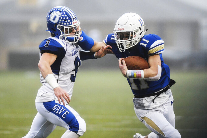 """FILE - In this Dec. 14, 2019, file photo, Newtown's Mike Ricks (11) blocks Darien's Sam Wilson (9) as the Newtown Nighthawks take on the Darien Blue Wave Class LL state football championship at Trumbull High School in Trumbull, Conn. The governing body of high school sports in Connecticut publicly released its plans for restarting interscholastic sports for the fall of 2020, proposing a shortened season that officials said will be """"fluid"""" based on changing COVID-19 health metrics. (Kassi Jackson/Hartford Courant via AP, File)"""
