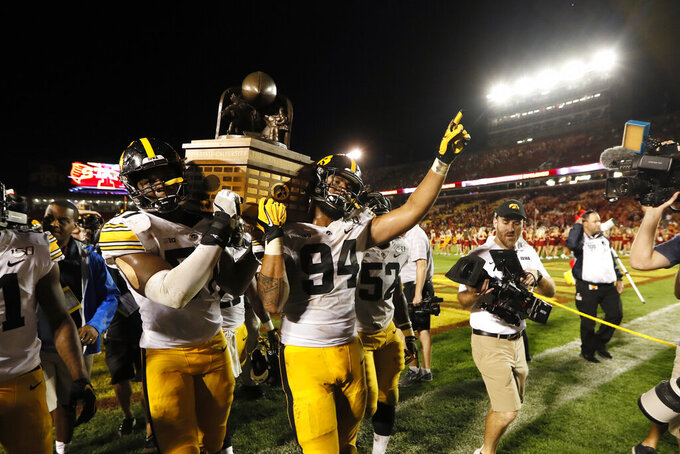 Iowa's Chauncey Golston, left, and A.J. Epenesa (94) carry the Cy-Hawk trophy off the field after the team's NCAA college football game against Iowa State, Saturday, Sept. 14, 2019, in Ames, Iowa. Iowa won 18-17. (AP Photo/Charlie Neibergall)