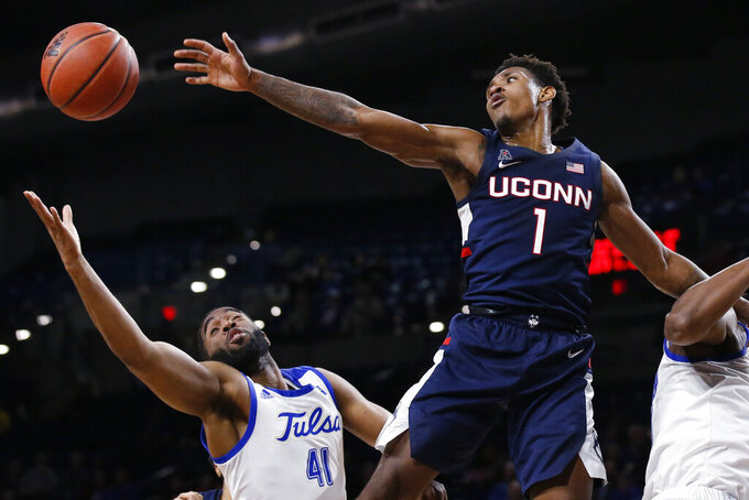 Connecticut guard Christian Vital (1) and Tulsa forward Jeriah Horne (41) reach for the ball during the second half of an NCAA college basketball game in Tulsa, Okla., Thursday, Feb. 6, 2020. (AP Photo/Sue Ogrocki)