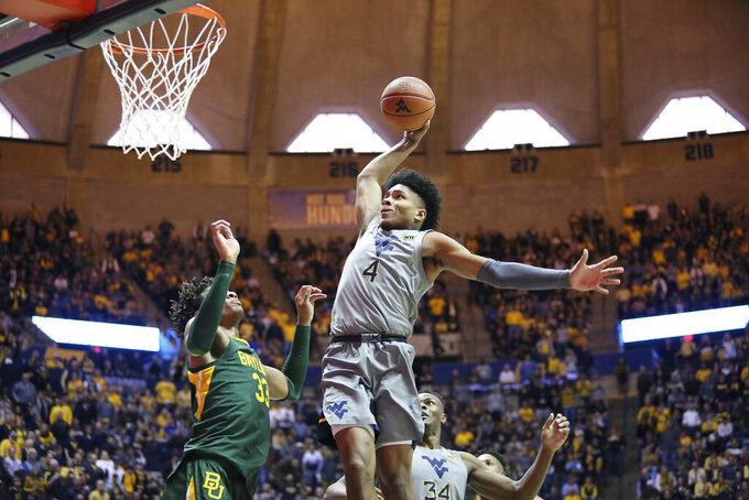 West Virginia guard Miles McBride (4) shoots while defended by Baylor forward Freddie Gillespie (33) during the second half of an NCAA college basketball game Saturday, March 7, 2020, in Morgantown, W.Va. (AP Photo/Kathleen Batten)