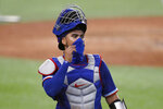 Texas Rangers catcher Robinson Chirinos adjusts his mask as he walks back to the dugout during a baseball practice at Globe Life Field in Arlington, Texas, Thursday, July 9, 2020. (AP Photo/Tony Gutierrez)